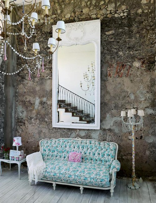 An exposed brickwall, a colourfull sofa and an oversized mirror creates a chic vintage and romantic focal point.