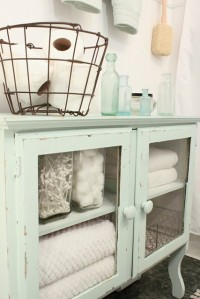 Sea green bathroom cabinet with glass doors and wire basket ontop.