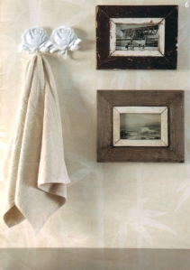 Lovely wallpaper for bathroom with rustic picture frames and towel hook.