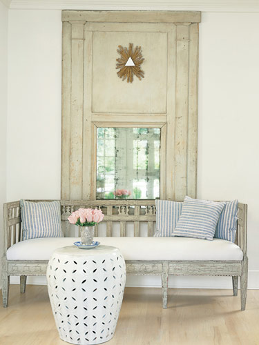 Gorgeous sofa with wood detail and an oversized mirror creates a lovely romantic feel.