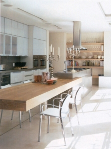 Multi level island using two different surfaces - dining part in wood adds warmth while the stainless steel surfaces are better suited for cooking and preparing food as it does not stain.